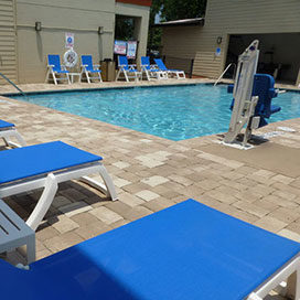 outdoor swimming pool with lounge chairs around and pool lift